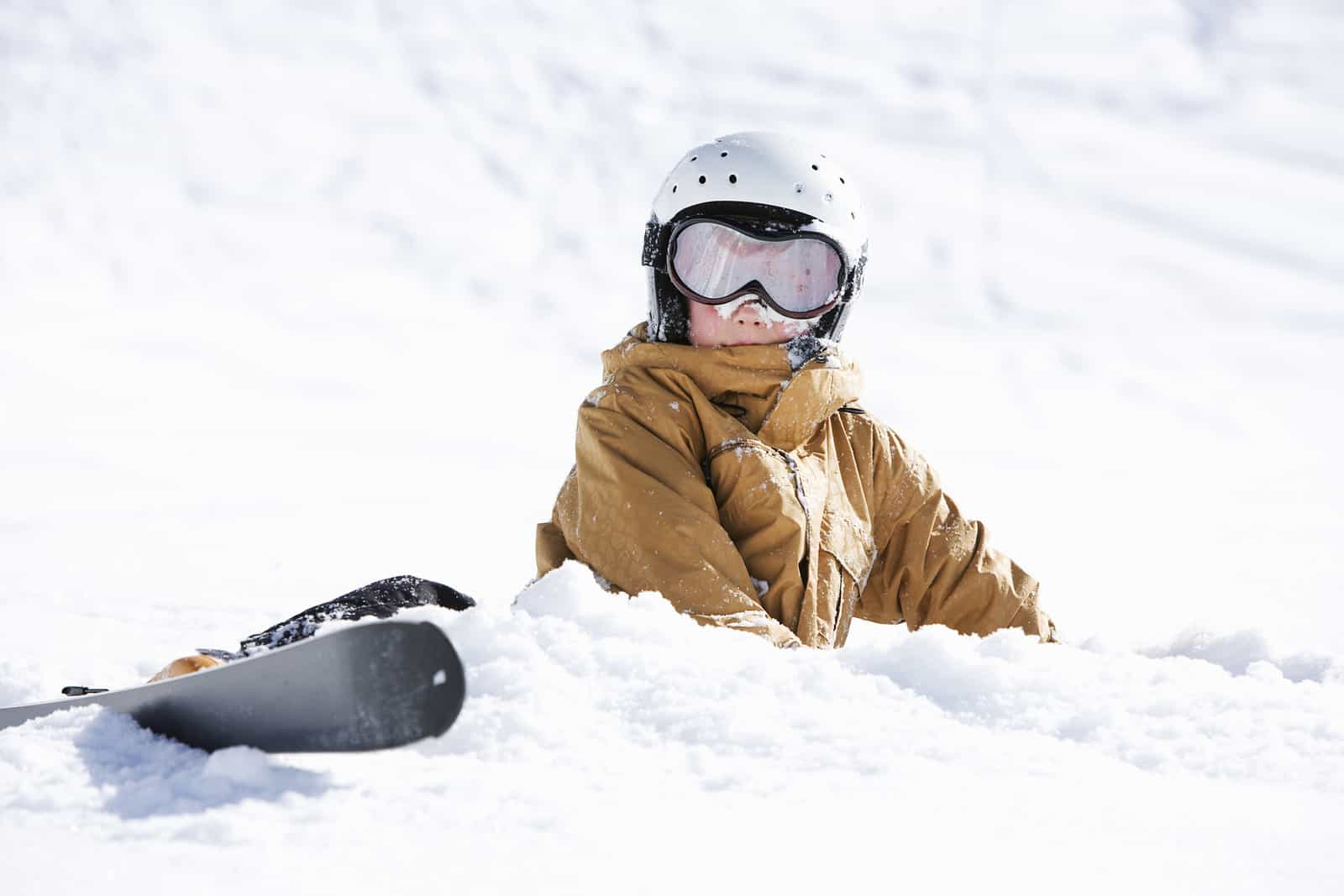 child on skis sitting in snow